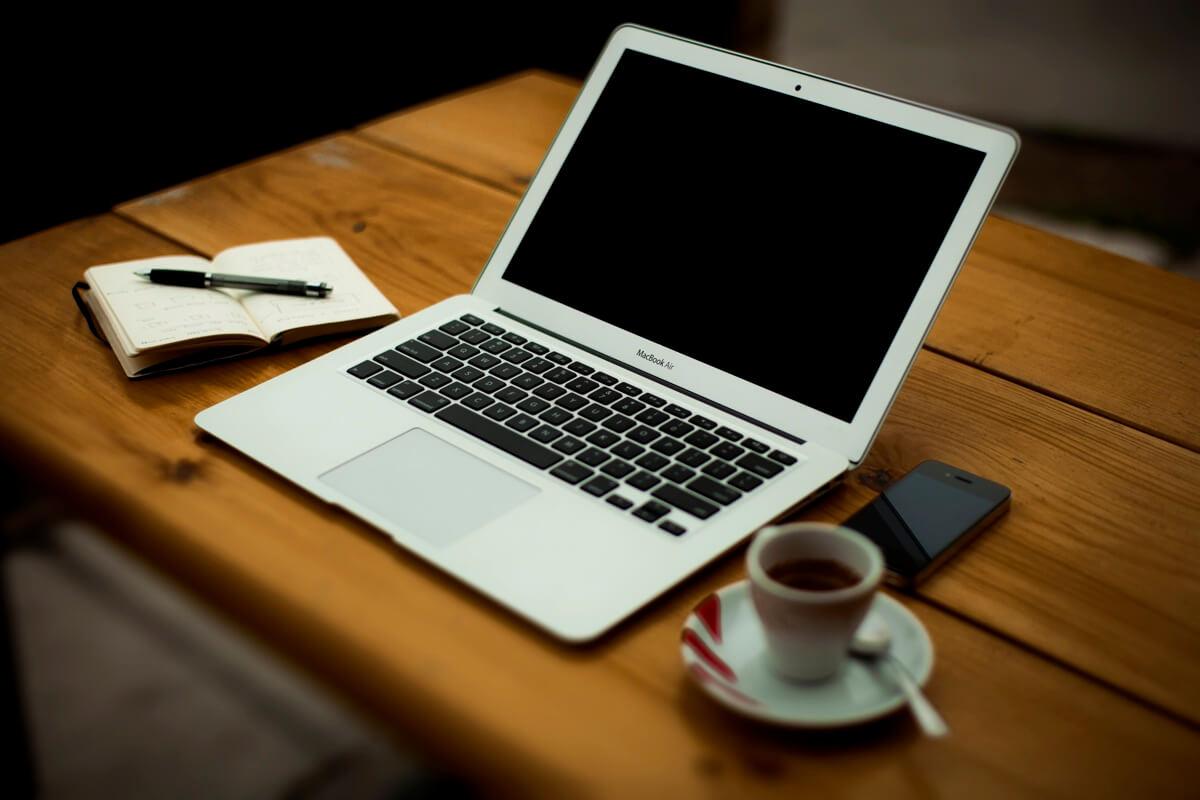 Ein Laptop, ein Notizblock, ein Handy und eine Tasse Espresso auf einem Holztisch