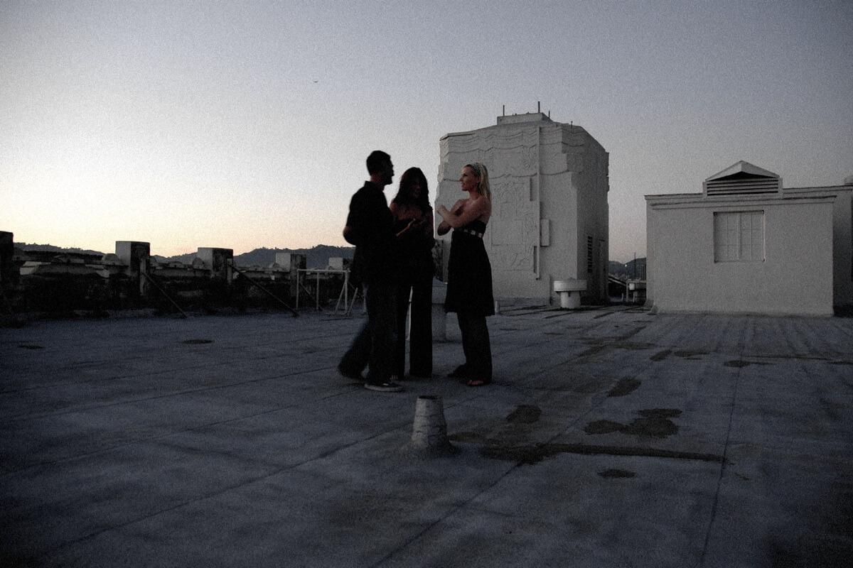 Ein Mann und zwei Frauen unterhalten sich bei Sonnenuntergang auf einem Hausdach in der Stadt