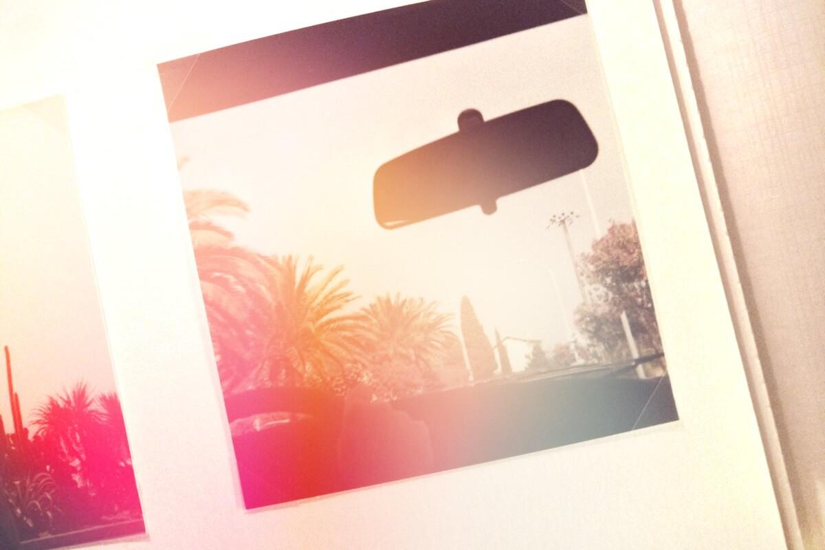 Ausblick aus einem Auto auf eine sonnenüberflutete Straße mit Palmen