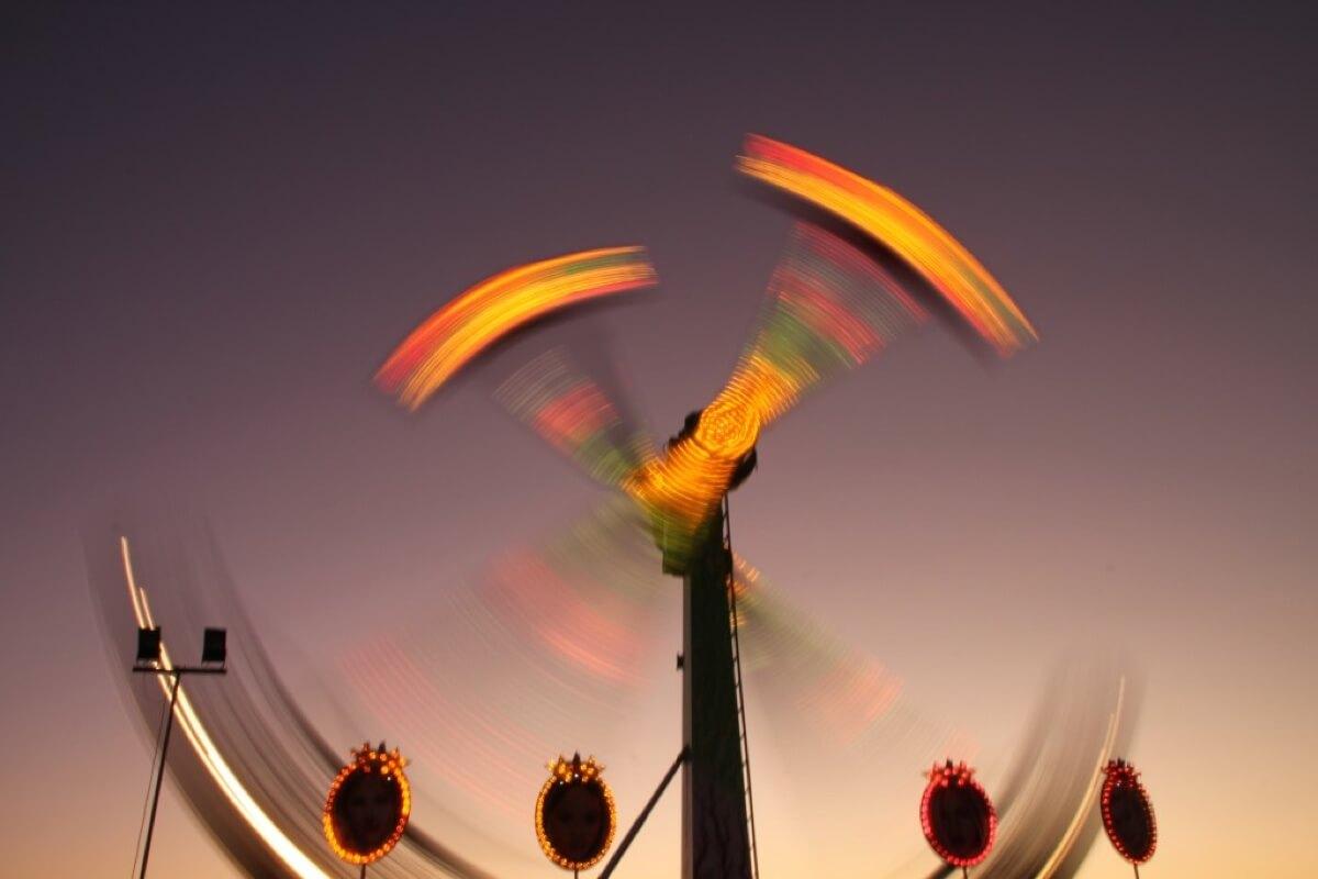 Ein sich schnell drehendes Fahrgeschäft auf einer Kirmes kurz vor Sonnenuntergang