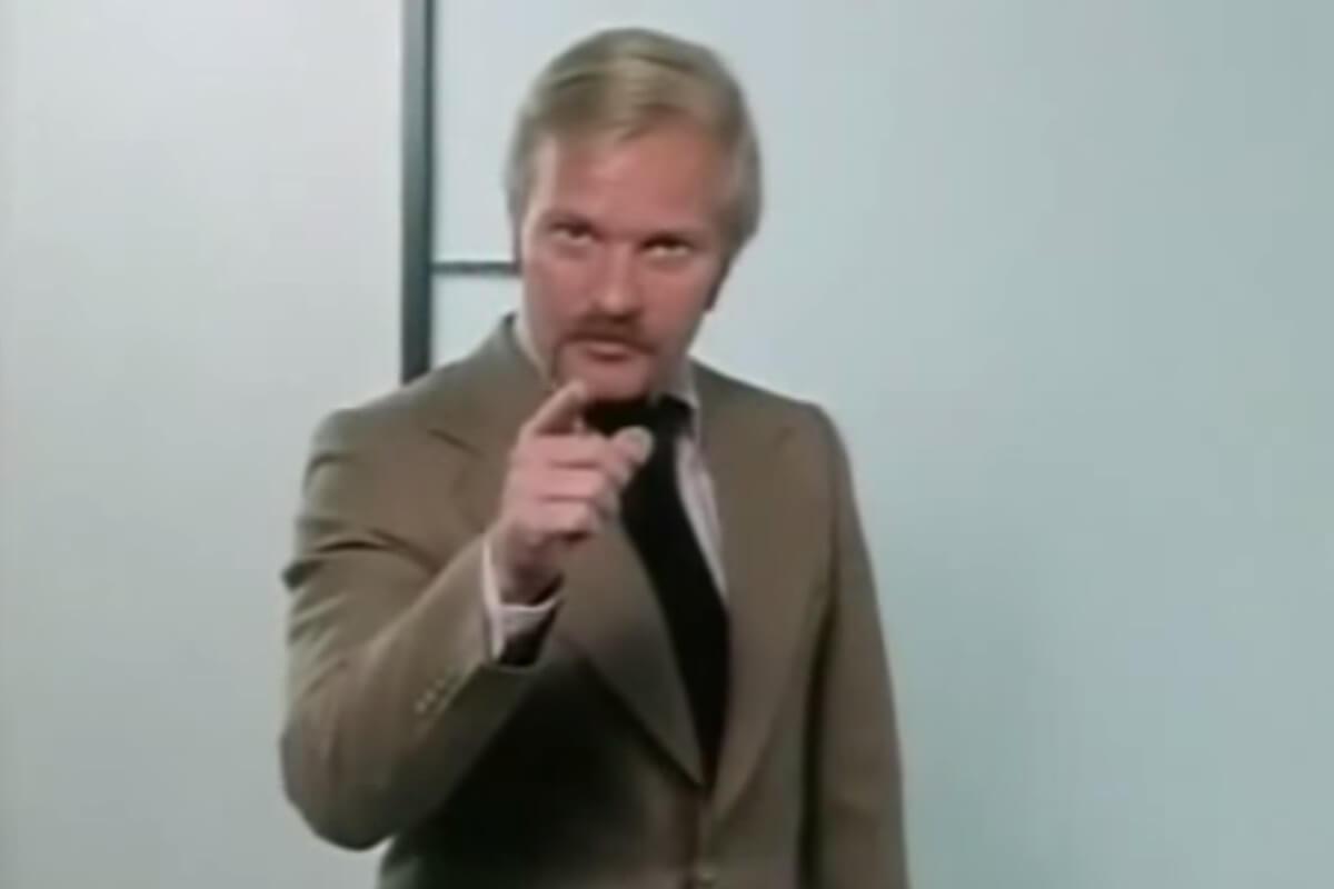 Ein Mann mit Schnauzbart zeigt mit dem Finger in die Kamera