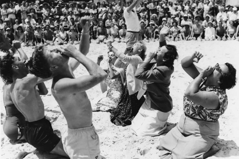 Schwarz-Weiß-Foto von Menschen, die an einem Strand ein Trinkgelage feiern