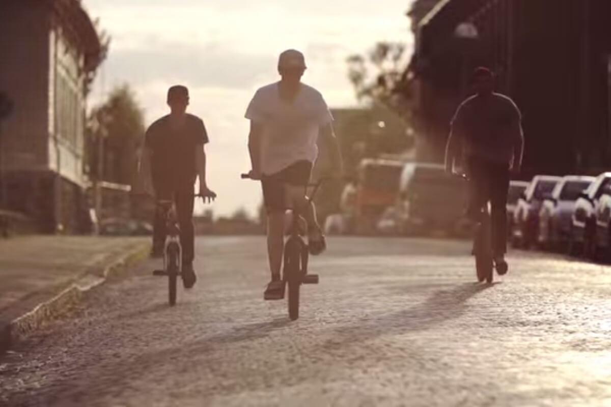 Drei Jugendliche auf BMX-Rädern fahren bei Sonnenuntergang eine Straße hinunter