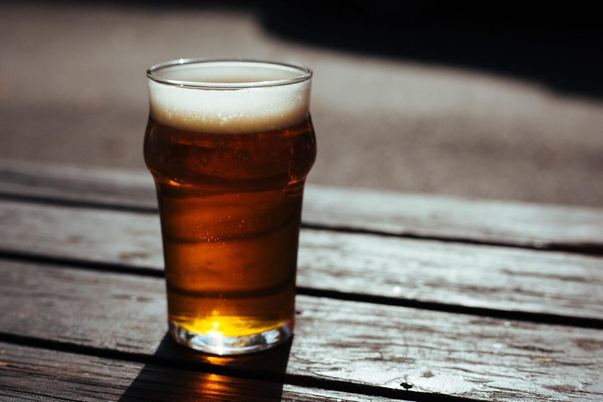 Ein Glas dunkles Bier steht auf einem Holztisch
