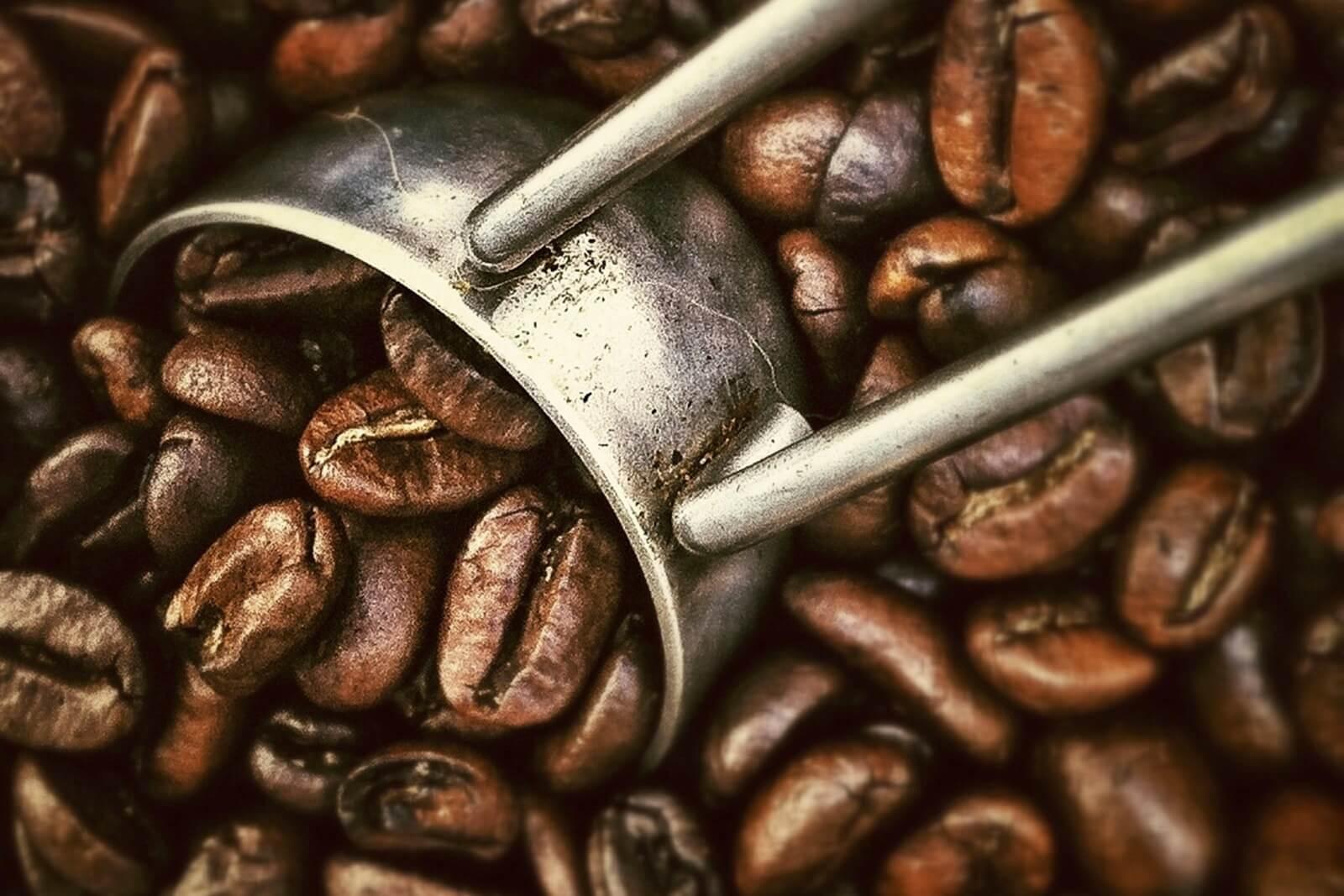 Nahaufnahme eines Metall-Löffels und von Kaffeebohnen