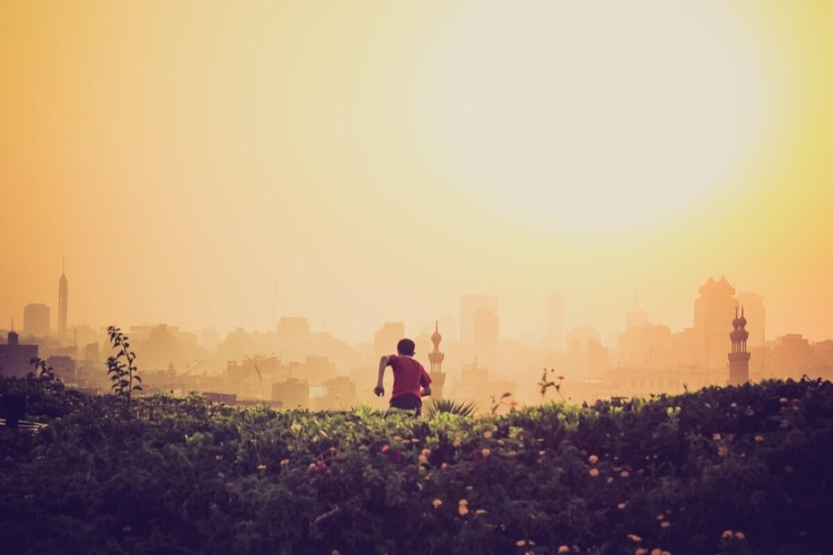 Ein Sportler läuft im Sonnenuntergang einen Hügel vor der Skyline einer Großstadt hinunter