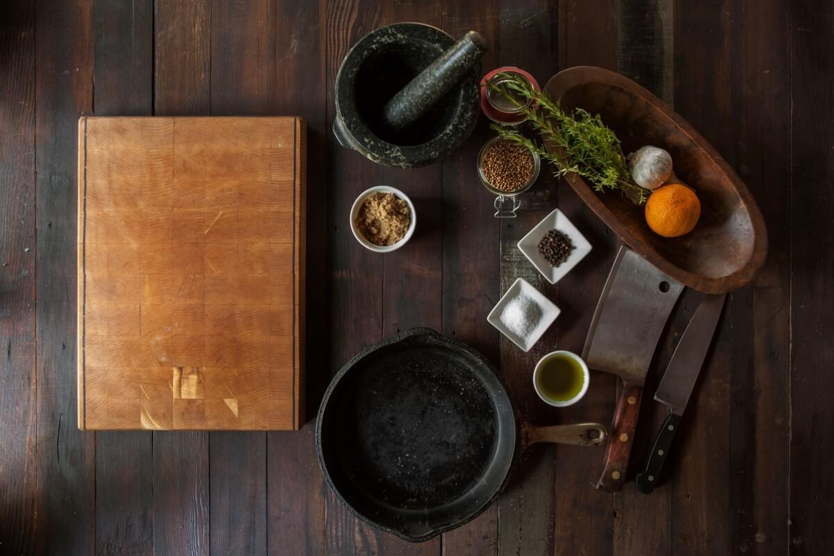 Ein Küchentisch mit diversen Kräutern, Gewürzen, einem Holzbrett und einem Mörser von oben aufgenommen