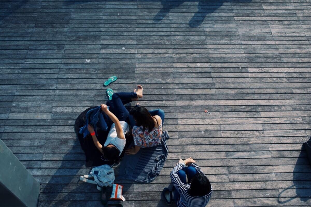 Eine Gruppe junger Menschen, von oben fotografiert, sitzt auf einem Holzsteg