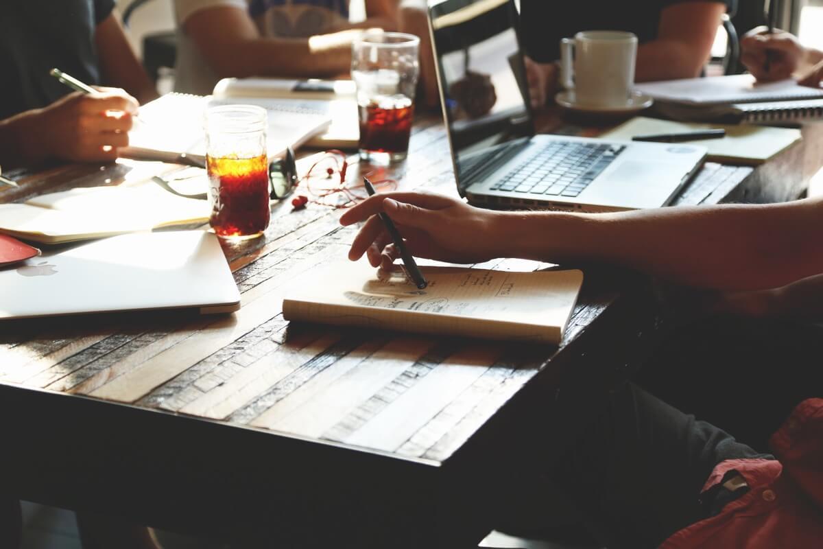 Aufnahme eines Schreibtischs mit Laptops und Notizheften, an dem mehrere Menschen arbeiten