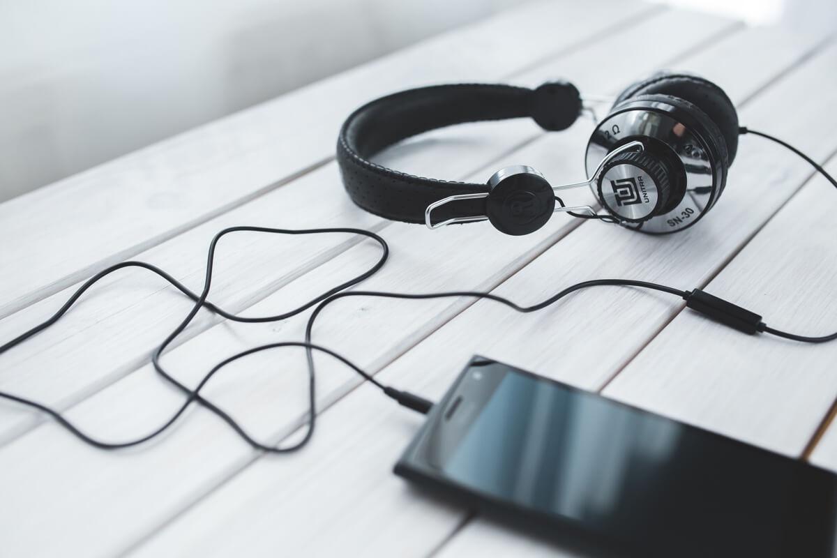 Ein Smartphone mit Kopfhörern liegt auf einem Holztisch