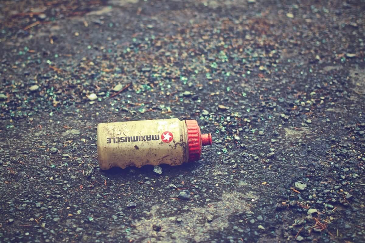 Eine Flasche für Sportgetränke liegt auf der Straße