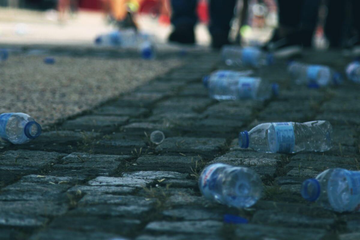 Nach einem Straßenlauf liegen leere Wasserflaschen auf einem Kopfsteinpflaster