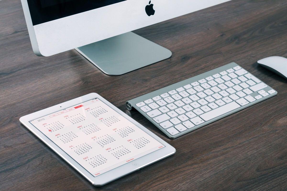 Aufnahme eines Apple-Computers und eines iPads, auf dem eine Kalender-App geöffnet ist