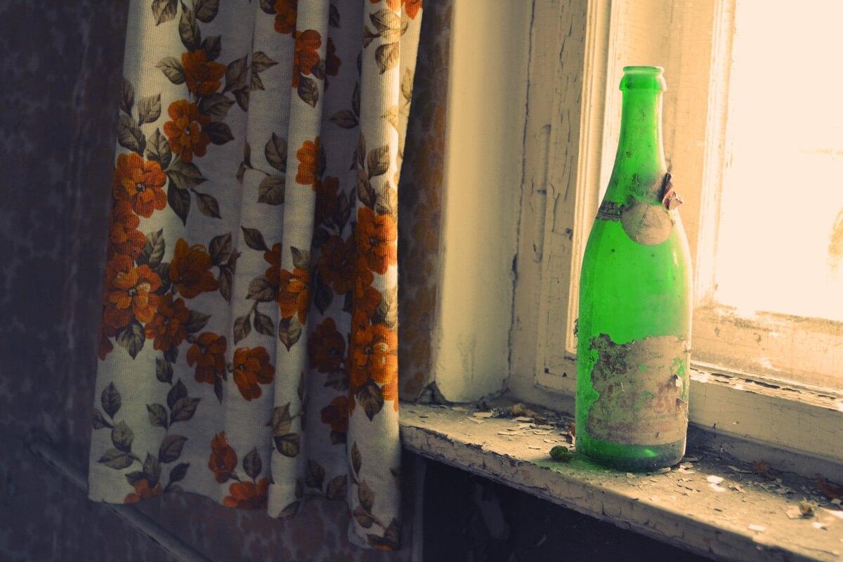 In einem verlassen wirkenden Haus steht eine Weinflasche auf einem Fensterbrett