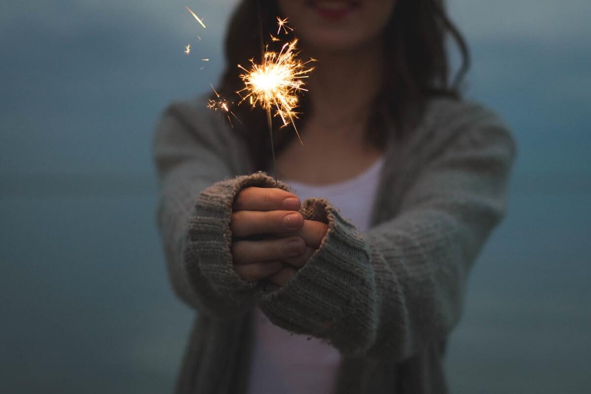 Eine Frau hält eine brennende Wunderkerze in der Hand