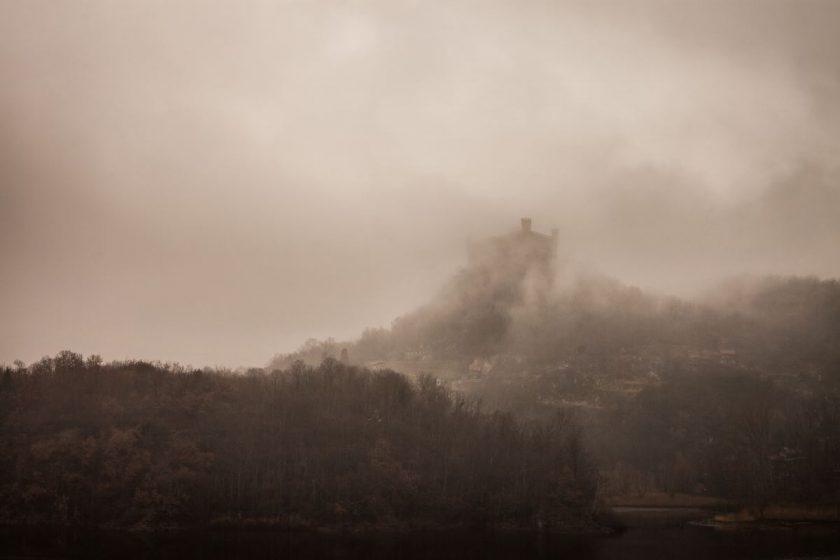 Auf einem nebelverhangenen Berg ist ein Schloss zu sehen
